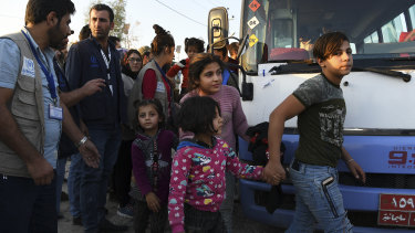 A group of Syrians disembark from one of the buses that brought  hundreds of refugees to Bardarash refugee camp in Iraqi Kurdistan.