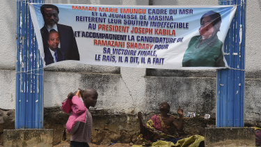 A child street beggar walks past a woman selling medicine on a street in Kinshasa under a banner supporting outgoing President Joseph Kabila and his hand-picked replacement, Emmanuel Ramazani Shadary.