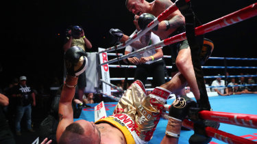John Wayne Parr punches  Anthony Mundine out of the ring at the Brisbane Exhibition and Convention Centre.