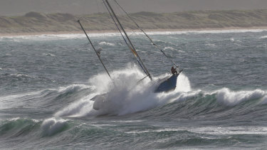 A crew member struggles to stand on the out-of-control yacht.