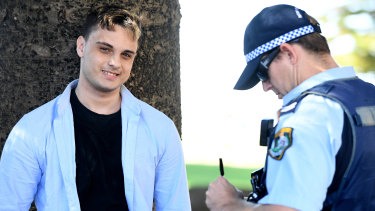 NSW Police detain a man after a confrontation with a photographer following a press conference.