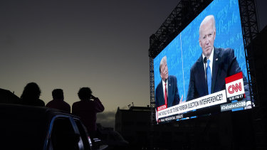 People watch from their vehicle as President Donald Trump, on left of video screen, and Democratic presidential candidate former Vice President Joe Biden speak during a Presidential Debate Watch Party at Fort Mason Center in San Francisco