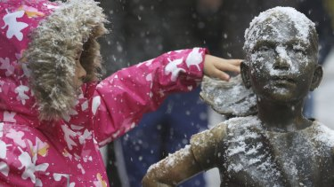 A young girl brushes off snow on the Fearless Girl statue in lower Manhattan.