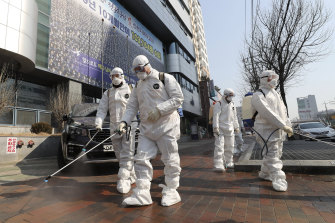 Workers wearing protective gears spray disinfectant against the new coronavirus in front of a church in Daegu, South Korea, where dozens of cases are linked to one church.