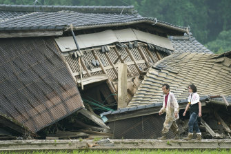 A couple walks in front of houses damaged by flood in Kuma village, Kumamoto prefecture, south-western Japan, on Sunday.