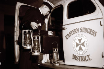 """Driver N. Hanson, who drives the all-night emergency 'maternity truck' of Eastern Suburbs Ambulance, was ready with storm-lanterns in case of a sudden call."" October 14, 1945"
