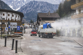 A truck equipped with a snow cannon fed with diluted hydrogen peroxide sanitises the streets in Selva di Val Gardena, Northern Italy, on Thursday.