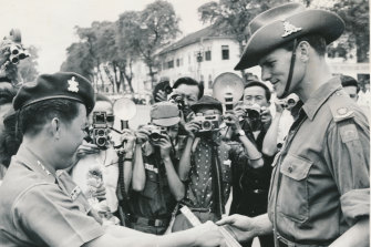 Major Peter Tedder, commander of the 105th Field Battery, is presented with a silver-mounted cane by Vietnamese Major General Tran Ngoo Tam.