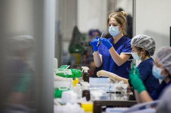 Medical staff prepare vaccine doses at a Melbourne vaccination hub.