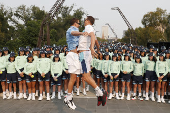 Bob and Mike Bryan bust out their trademark chest-bump ahead of the 360-strong Australian Open ballkids contingent.