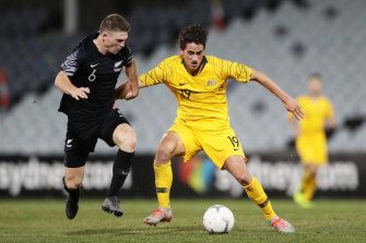 Lachlan Wales is challenged by New Zealand's Dane Schnell.