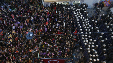 A phalanx of Turkish police officers in riot gear, right, block protesters during a rally in central Istanbul's Istiklal Avenue  to mark the United Nations' International Day for the Elimination of Violence Against Women on Sunday.