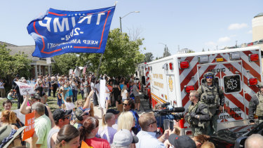 A small group of President Donald Trump supporters gather among protesters against the President's visit outside Miami Valley Hospital in Dayton, Ohio.