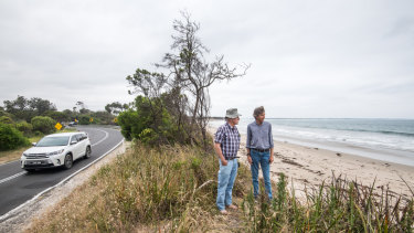 Locals Dave Sutton (left) and Phillip Heath on the remaining strip separating the surf beach from the road at Inverloch, where erosion has caused major problems.