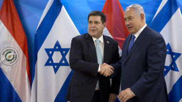 Israeli PM Benjamin Netanyahu, right, shakes hands with Paraguayan President Horacio Cartes. Paraguay opened its new embassy in Jerusalem on Monday local time.