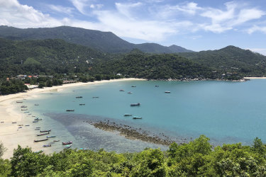 Fishing vessels and boats used to ferry tourists sit idle along a deserted beach on the popular tourist island of Koh Phangan, Thailand, on Sunday, July 5, 2020. Tourism in Thailand has taken a severe hit because of travel restrictions prompted by the coronavirus pandemic, leaving many popular beaches nearly empty. (AP Photo/Adam Schreck)