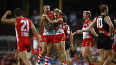 Callum Mills of the Swans celebrates a goal with Lance Franklin.