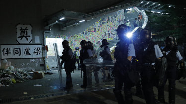 Police officers in anti-riot gear clear protesters from the Legislative Council in Hong Kong.