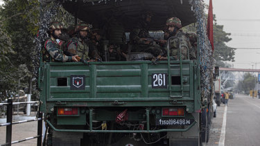 Indian army soldiers in a vehicle get ready for a flag march during a curfew in Gauhati, India.