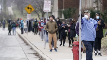 Voters masked against coronavirus line up at a high school for Wisconsin's primary election in Milwaukee on April 7.