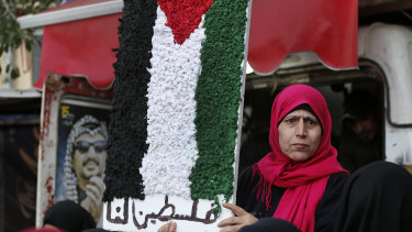"""A Palestinian woman holds a symbolic of the Palestine flag with Arabic words that read: """"Palestine for us"""" at a refugee camp, south of Beirut."""