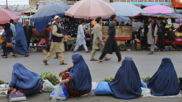 Women selling vegetables wait for customers at a market in Kabul, Afghanistan.