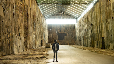 Ibrahim Mahama stands inside Cockatoo Island's Turbine Hall surrounded by his vast art installation No Friend but the Mountains