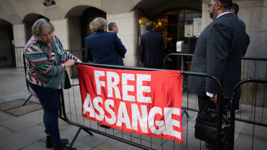 A supporter of the Wikileaks founder Julian Assange hangs a banner outside the Old Bailey on September 14, 2020 in London.