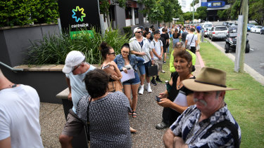 Queues stretch down the street outside a Centrelink office on the Gold Coast.