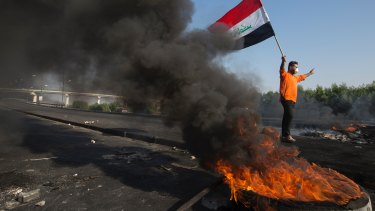 Anti-government protesters light fires to close streets and bridges during protests in Basra, Iraq.