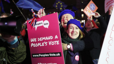 Anti-Brexit demonstrators react after the results of the vote on British Prime Minister Theresa May's Brexit deal were announced in Parliament Square in London.