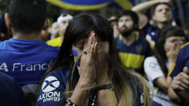 A Boca fan reacts to the loss as she watches on television in Buenos Aires.