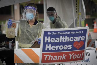 A worker hands out testing kits at a mobile coronavirus testing site in Los Angeles this week.