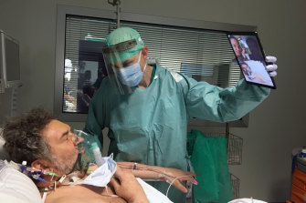 Doctor Matteo Flippini holds a tablet for a patient Alessandro Mattinzoli to talk to his relatives from the intensive care unit of a hospital in Brescia.