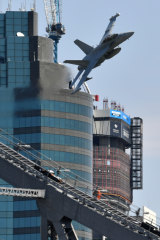 A Royal Australian Air Force EA-18G Growler flies over the Brisbane skyline as part of the final rehearsal for Riverfire.