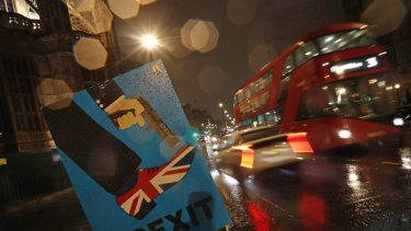 Vehicles drive past an anti-Brexit placard near the British Parliament on Tuesday.