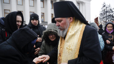 An Orthodox believer kisses the hand of a priest of the Ukrainian Orthodox Church of Moscow Patriarchy during a protest against the creation of a Ukrainian independent church, in front of the parliament building in Kiev, Ukraine, last week.