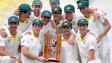 Long wait: Australia's captain Tim Paine holds the trophy as he poses with teammates after they finally broke through for a series victory.