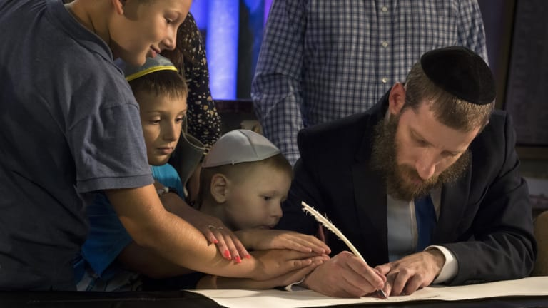 Members of Lithuania's Jewish community write in a new Torah dedicated to unity and goodness, commemorate death of family members and remember all who have died or been tortured in the Holocaust.