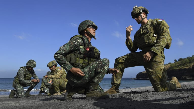 Australian Army Sapper Nicholas Field (right) and Lance Corporal Callum Leete (second from left) instruct members of the Philippines military.