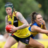 Burning bright: Tiger Tayla Stahla makes a quick getaway as West Coast's Hayley Bullas attempts a tackle during the practice match at Punt Road Oval in Richmond.