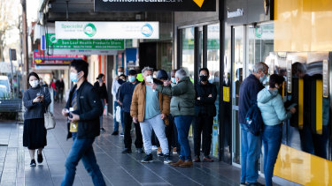 People line up outside the Commonealth bank in Campsie, a growing Covid-19 hot spot in the Bankstown Canterbury LGA, during Sydney's lockdown. 27th July 2021 Photo: Janie Barrett