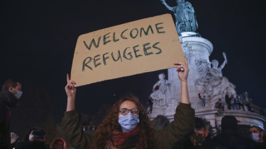 A demonstrator holds a banner during a rally on the Place de La Republique in Paris on Tuesday, after migrants were ejected by police by force.
