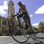 Coming through: Jeff McClurg rides his  penny farthing down Stawell's main street.