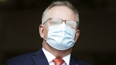 Prime Minister Scott Morrison, seen here with fogged glasses from wearing a mask, has flagged more funding will come for aged care.