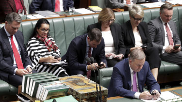 Top Labor frontbenchers on their mobile phones during question time on Monday.