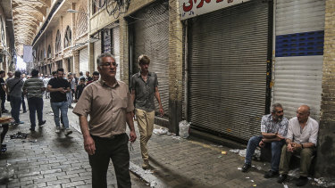 People walk through the old Grand Bazaar where shops are closed after a protest, in Tehran, on Monday.