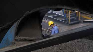 A worker monitors the coal dumping process at the Caofeidian Port in Hebei Province.