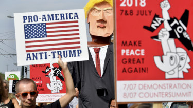 A protester marches next to giant puppet of US President Donald Trump as he holds a sign which reads 'Pro-America, Anti-Trump' during a demonstration in Brussels on Saturday.