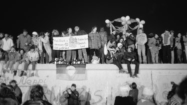 Revellers gather on the Berlin Wall to celebrate the New Year and the effective end of the city's partition, on December 31, 1989. A banner reads ''Good luck and peace for a new Germany - East Greets West''.